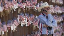 A Southern Arizona rancher, stands at the border wall with Mexico on Sunday, Aug. 15, 2010 in Hereford, Ariz. He was attending the United Border Coalition Tea Party Rally in support of Arizona's immigration law, SB1070 with conservative tea party activists along a remote stretch of the Arizona-Mexico border about 113 kilometers west of Nogales. (Matt York/AP/Matt York/AP)