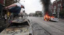 A man jumps on the shell of burned-out cruiser 3251 (which was set on fire at 6 p.m.), as cruiser 766 is engulfed in flames. Fire truck makes first appearance on Queen at about 8 p.m. (MARK BLINCH/Mark Blinch/Reuters)