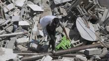 A member of the Issa family salvage belongings from their house that was destroyed in an overnight Israeli strike at Shati refugee camp, in the northern Gaza Strip on Aug. 2. (Hatem Moussa/Associated Press)
