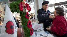 A Royal Canadian Legion member pins a Remembrance Day poppy on a woman's coat at Toronto's Eaton Centre on Nov. 8, 2010. (Deborah Baic/Deborah Baic/The Globe and Mail)