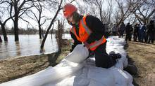 Melanie Schultz has taken a few days off work to build a dike to protect her home from the rising Red River in Winnipeg's north side on April 14, 2011. About 350 students volunteered in Winnipeg's north end to get sandbagging done in vulnerable areas. (John Woods/JOHN WOODS/THE GLOBE AND MAIL)