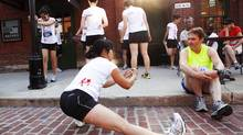 Runners from the New Balance team stretch before running in the Acura 10 Miler. (Della Rollins For The Globe and Mail)