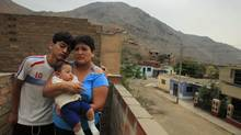 Giovanna Figueroa (wife of injured Peruvian Javier Alba) accompanied by her two sons Sulman, 14, and Ashraf Alba (six months old) at their home in Comas, Peru. (Pilar Olivares For The Globe and Mail/Pilar Olivares For The Globe and Mail)