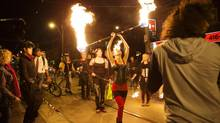 Partiers walk down Queen Street West with fire shutting down traffic to celebrate the 10th anniversary of the blackout in Toronto during a street party on Queen West Street (Della Rollins For the Globe and Mail)