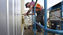 Temporaryforeignworker David Beattie, from Scotland installs cladding while working on the construction of a new police station in Edmonton, Monday April 30, 2012. (Jason Franson for The Globe and Mail)