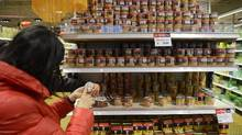 File photo of customers checking prices in a supermarket in Toronto. (Fred Lum/The Globe and Mail)