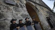 Colombian riot police officers stand guard at an entrance to Cartagena's old city, near the site of this weekend's Summit of the Americas. (Ricardo Moraes/Reuters)