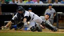 Toronto Blue Jays third baseman Brett Lawrie (rear) scores a run as the ball gets away from New York Yankees catcher Brian McCann (front) in the 4th inning during the MLB baseball game at Yankee Stadium. (Robert Deutsch/USA Today Sports)