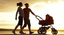 Silhouettes Of Happy Parents Walking With Child And Baby's Stroller On The Seacoast (YanLev/Photos.com)
