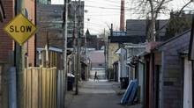 A pedestrian makes their way across a laneway between Gladstone and Beaconsfield avenues in Toronto. (Darren Calabrese for The Globe and Mail)