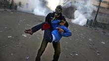 An Egyptian protester evacuates an injured boy during clashes near Tahrir Square, Cairo, Jan. 25, 2013. (Khalil Hamra/AP)