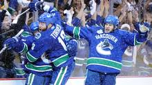 Raffi Torres of the Vancouver Canucks celebrates with his teammates Victor Oreskovich and Kevin Bieksa after a goal late in the third period. (Harry How/2011 Getty Images)