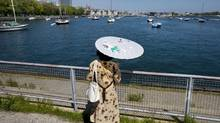 A woman hides from the sun under a parasol on the Toronto waterfront during an extreme heat alert for the city on May 24, 2010. (Darren Calabrese/For The Globe and Mail/Darren Calabrese/For The Globe and Mail)