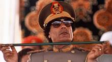 In this Sept. 1, 1987 file photo, Libyan leader Col. Moammar Gadhafi, holds a baton as he sits to review Libyan troops during the 18th anniversary celebration of Libya's revolution in Tripoli. (AP/John Redman/AP/John Redman)