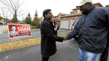 Neethan Shan shakes voter Dexter's (no last name given) hand after putting a sign on his lawn in Ward 42 in the Morningside and Finch area in Toronto, Ontario, Canada. (Deborah Baic/Deborah Baic/The Globe and Mail)