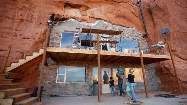 """Enoch Foster, a fundamentalist Mormon who practices polygamy, along with his first wife Catrina Foster and several of his 13 children from his two wives, enters the Charity House at the Rockland Ranch community outside Moab, Utah, """"The Rock,"""" as it is referred to by the approximately 100 people living there in about 15 families, was founded about 35 years ago on a sandstone formation near Canyonlands National Park. (Jim Urquhart/REUTERS)"""