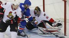 Ottawa Senators' goaltender Craig Anderson (41) makes a save on a shot by New York Rangers' J.T. Miller, centre, during the third period of an NHL hockey game in New York, Sunday, Nov. 27, 2016. (Rich Schultz/AP)