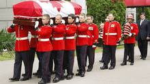Members of the Royal Canadian Regiment carry the casket containing the remains of Romeo LeBlanc, former governor-general of Canada, out of the Memramcook Institute toward a hearse for transport to a state funeral service at Saint Thomas church in Memramcook, NB. (PAUL DARROW)