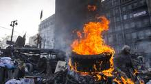A tire burns for heat and as a smokescreen as protesters in Kiev man their makeshift barricade on Jan. 26, 2014.