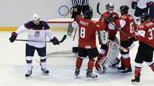 USA forward Zach Parise skates off the ice as Canadian players celebrate after a men's semifinal ice hockey game at the 2014 Winter Olympics, Friday, Feb. 21, 2014, in Sochi, Russia. Canada won 1-0 to advance to the gold medal game.