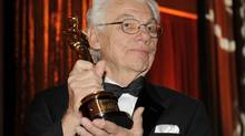 In this Nov. 14, 2009 file photo, cinematographer Gordon Willis poses with his honorary Oscar following The Academy of Motion Picture Arts and Sciences 2009 Governors Awards in Los Angeles. (Chris Pizzello/AP)