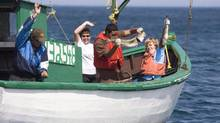 People show off their catch as they fish in Bay Bulls, N.L. in 2007. (Jonathan Hayward/The Canadian Press)