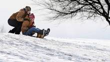 Stephens City, Va., residents Amy Frederick, 15, seated, and Allison Wilfong, 20, enjoy a wooden toboggan ride Tuesday, March 4, 2014, on the campus of Shenandoah Valley Christian Academy in Stephens City, Va. (Jeff Taylor/The Associated Press)