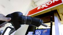 A motorist pumps gas at an Exxon station. (Don Ryan/AP Photo)