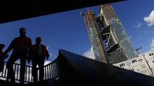 Construction workers walk down the stairs on a bridge next to the construction site of the new headquarters of the European Central Bank in Frankfurt. (KAI PFAFFENBACH/REUTERS)
