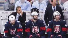 Team USA head coach John Tortorella, back left, and assistant coach Phil Housley, back right, look on as Team USA players Blake Wheeler (26) Ryan Kesler (17) and David Backes (42) watch the game against Canada during third period World Cup of Hockey action in Toronto on Tuesday, September 20, 2016. (Nathan Denette/THE CANADIAN PRESS)