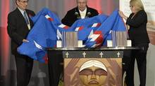 Justice Murray Sinclair (centre) and Commissioners Chief Wilton Littlechild (left) and Marie Wilson pull back a blanket to unveil the Final Report of the Truth and Reconciliation Commission of Canada on the history of Canada's residential school system, in Ottawa on Tuesday, Dec. 15, 2015. THE CANADIAN PRESS/Adrian Wyld