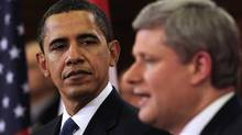 U.S. President Barack Obama listens to Canadian Prime Minister Stephen Harper hold a news conference on Parliament Hill in Ottawa, February 19, 2009. (LARRY DOWNING/REUTERS)