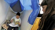"Monique Michelle watches as Jesse George choses to sit in the ""bunny hole"" to read her book in a special FASD program at David Livingston Community School in Winnipeg, Tuesday, May 11, 2010. (John Woods/The Globe and Mail)"