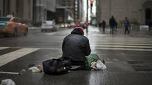 Daniel stays warm sitting over a grate on King St. West and Bay St. that releases warm steam from below, on March 3 2016. Daniel is trying to move from his current TCHC housing which has bedbugs and is currently staying with friends until his housing situation is resolved. (Fred Lum/The Globe and Mail)