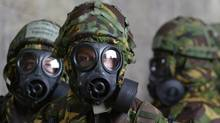 British Royal Air Force personnel wear full biological and chemical protective suits after a warning of a scud attack from Iraq toward their base in Kuwait in March of 2003. (RUSSELL BOYCE/Russell Boyce/Reuters)