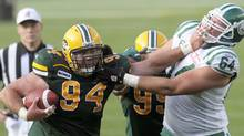 Edmonton Eskimos' Dario Romero carries the ball against Saskatchewan Roughriders' Dan Goodspeed (R) after recovering a fumble during the first half of their CFL football game in Edmonton August 28, 2010. REUTERS/Dan Riedlhuber (DAN RIEDLHUBER)