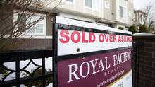 """A real estate sign reading """"Sold Over Asking"""" stands on display outside a townhouse in Richmond, British Columbia, Canada, on Sunday, Dec. 11, 2016. (Ben Nelms/Bloomberg)"""