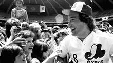 In this June 24, 1983 file photo, Montreal Expos catcher Gary Carter is mobbed by admiring fans at camera day prior to a baseball game against the Pittsburgh Pirates in Montreal. (Bernard Brault/THE CANADIAN PRESS/Bernard Brault/THE CANADIAN PRESS)
