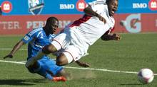 New England Revolution's Andrew Farrell is tripped by Montreal Impact's Sanna Nyassi during first half MLS action Saturday, October 12, 2013 in Montreal. (Paul Chiasson/THE CANADIAN PRESS)