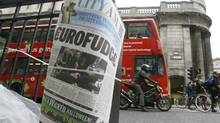 A financial newspaper is fixed to a pillar by a newspaper seller with The Bank of England building behind, in the city of London, Thursday, Oct. 27, 2011. (Kirsty Wigglesworth/AP)