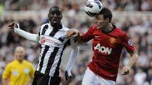 Newcastle United's Demba Ba, left, challenges Manchester United's Jonny Evans during their English Premier League soccer match in Newcastle, northern England, October 7, 2012. (Reuters)