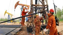 Workers from China's Sinopec Corp. work on an oil field in Puyang county of Henan province, central China. (CHINA NEWSPHOTO/REUTERS)
