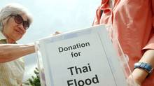 A donor puts money into a donation box for the Thai flood victims, at a Buddhist temple in Kuala Lumpur on Feb. 27, 2011. (STR/AFP/Getty Images)