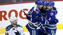 Vancouver Canucks Cody Hodgson (R) celebrates his second goal against the San Jose Sharks with teammates Jannik Hansen (36) and Mason Raymond in front of Sharks Michal Handzus during the third period of their NHL hockey game in Vancouver, British Columbia January 21, 2012. (BEN NELMS/REUTERS)