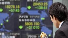 A man looks at an electronic stock board of a securities firm in Tokyo, Monday, April 17, 2017. Asian shares were mixed Monday amid continuing worries about tensions on the Korean Peninsula, while Hong Kong and Australian markets were closed for the Easter holidays. (Koji Sasahara/AP)