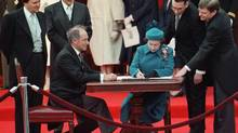 The Queen signs Canada's constitutional proclamation in Ottawa on April 17, 1982 as Prime Minister Pierre Trudeau looks on. (RON POLING/Canadian Press)