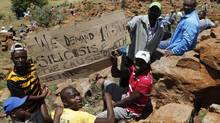 Striking miners hold a placard after gathering on a hill outside an AngloGold mine in Carletonville, northwest of Johannesburg Oct. 17, 2012. (SIPHIWE SIBEKO/REUTERS)