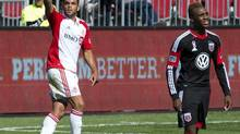Toronto FC midfielder Darel Russell (left) celebtares his goal as D.C. United forward Michael Seaton walks away during first half MLS action in Toronto on Saturday June 28, 2013. (Frank Gunn/THE CANADIAN PRESS)
