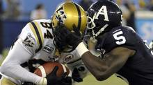 Toronto Argonauts defensive end Ejiro Kuale grabs hold of Winnipeg Blue Bombers wide receiver Greg Carr (L) during the first half of their CFL football game in Toronto September 24, 2011. REUTERS/Mike Cassese (Mike Cassese/Reuters)