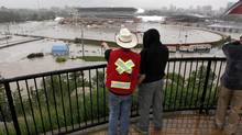 Calgarians look out over a flooded Calgary Stampede grounds and Saddledome in Calgary on June 21, 2013. (Jeff McIntosh/The Canadian Press)